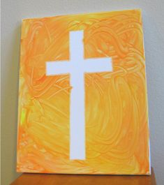 tape a cross onto canvas, let the kids fingerpaint (or use brush) around it, then remove the tape