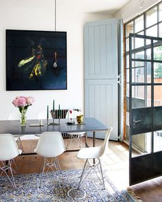 Airy dining space // eames Eiffel chairs // cast iron door frames // Persian rug // art