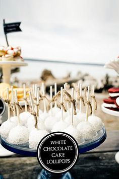 White chocolate cake pops are displayed on this nautical themed dessert table.