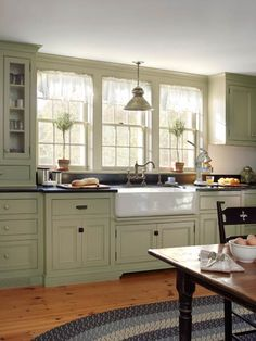 Double-hung windows and an apron sink echo the period look of this updated farmhouse kitchen | Photo: Tria Giovan green farmhouse, cabinet colors, farmhouse kitchen window, apron sink, old houses, farmhouse additions, old farmhouse cabinets, farmhouse sinks, farm sinks