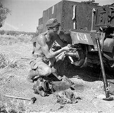 Canadian Private R. E. Hill repairing his Universal Carrier, Catania, Italy, August 22, 1943 / Le soldat R. E. Hill répare son porteur universel à Catane (Italie), le 22 août 1943