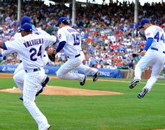 Chicago Cubs players click their heels as they take the field on Friday (7/27/12) in honor of Ron Santo's induction into the Baseball Hall of Fame. This was a signature move always made by Ron Santo when he played baseball for the Chicago Cubs.
