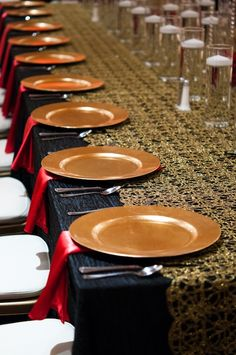 Indian reception with black table linen and gold overlay with red napkins and gold charger plates #indianwedding #reception