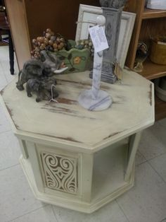 Another quality octagonal end table in heavy, heavy solid oak!  It has storage underneath with carved wood inset panels and has been painted cream, distressed, and finished with a stain/poly combo for an aged look and smooth surface.