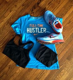 Blue Nike T-shirt with snappy #quote, black sports bra and shorts, and the cutest blue and coral sneakers!  #fitness #fashion