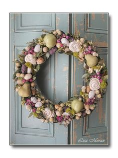 Beautiful apple and pear wreath with touches of pink and filled with nuts, roses, and dried materials.