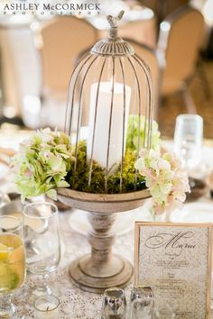 Simple birdcage centerpieces. Candle on moss with hydrangeas.
