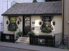 Tiny home - SO cute! I love the use of scrolled shelf brackets to look like shutters!