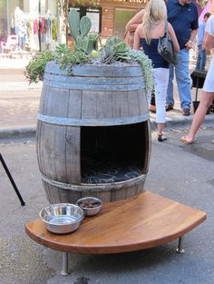 Old wooden barrel upcycled as a dog house (and planter)