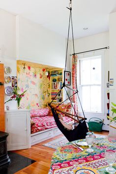 A daybed and a swing in Laurie and Bruce Rabe's kitchen for relaxing (and their younger, handicapped daughter loves to swing so they installed one in the kitchen since they spend a lot of time there) - the mural of flowers was painted by Laurie Rabe