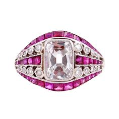 "Templier Art Deco Ruby Diamond Platinum Ring. The slightly dome-shaped ring centers 1 bezel-set rectangular cushion-cut diamond, approximately 1.61 carats, color: F-G, clarity: VS2, surrounded by 2 rows of round bezel-set diamonds and 3 rows of channel-set square step-cut rubies, approximately 1.16 carats. The ring is signed ""Templier, Paris"" (designer Raymond Templier). Total diamond weight for the ring is approximately 1.85 carats. Circa 1920"