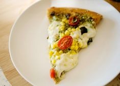 Corn, Pesto, and Tomato Pizza recipe - I made this Corn and Tomato Pizza before we left and it was summer on a piece of pizza.  Corn, fresh pesto, tomatoes, basil, and fresh mozzarella.  This pizza proves that going beyond sauce and cheese is worth the effort. #pizza #corn #tomato #pesto