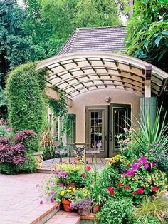 A Pergola Makes It:  We typically see pergolas standing alone in the yard, but here, a rounded pergola makes an entry something special. The structure's non-traditional shape works well with the house, and the style fits the informal plantings while creating an intimate patio useful for morning coffee or a  anytime with a couple of guests...