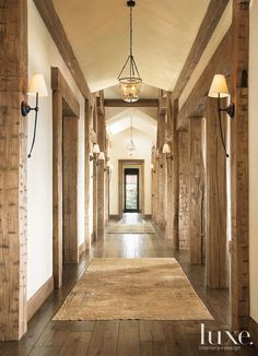 rustic hallway is illuminated by sconces and hanging light fixtures.