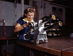 """October 1942. Inglewood, California. """"Young woman employee of North American Aviation working over the landing gear mechanism of a P-51 fighter plane."""""""