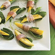 Prosciutto-Wrapped Mango Bites | For a simple, fresh appetizer, wrap mango slices and arugula in paper-thin slices of prosciutto.  | SouthernLiving.com