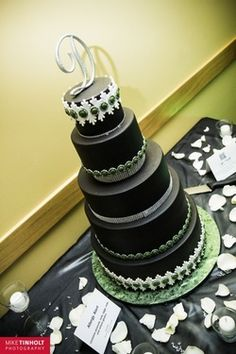 Black wedding cake with emerald & white jeweled brooch details with rhinestones. www.cakestudio.ca rhineston, jewel brooch, emerald, brooch detail, wedding cakes