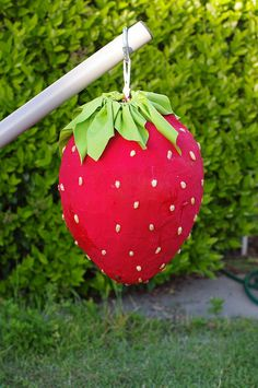 "Strawberry pinata ... ""Amelia and I made this strawberry pinata. I papier mache'd a large balloon, then filled it with candy & painted it red. Amelia and I glued peanuts all over it for teh seeds (botanically speaking, they're actually the fruits). I made fabric leaves (bracts) to top it off."""
