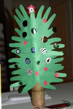 A Christmas tree art project using hand prints as the tree, a paper towel roll as the trunk, and bits and pieces of wrapping paper as ornaments. We had a lot of fun with this one!
