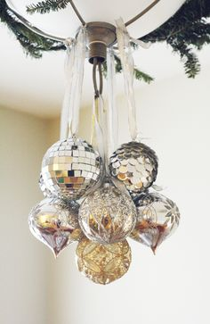Hang a group of similar colored ornaments to lighting with individual sheer ribbons; stagger by varying ribbon lengths.