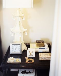 Table Clock Photo - A white chinoiserie lamp on a black bedside table