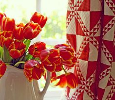 Delightful pitcher of red tulips with red quilt drapes  #flowers #floral