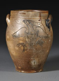 """Stoneware Jar with Incised Patriotic Eagle Decoration, Daniel Goodale Pottery, Hartford, Connecticut, early 19th century, two-gallon oval wide-mouth jar, with lug handles, decorated on the front with a spreadwing eagle with American shield with a star-spangled banner in its beak, and clutching an olive branch and a flag in its talons, impressed """"D. GOODALE. HARTFORD"""" on opposite shoulder, (cracks, chips), ht. 12 1/4 in. Provenance: Purchased from Joyce and Ron Basin."""