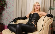 Gorgeous blonde wearing latex gloves a leather corset and Lycra stretch pants