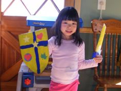 Silent K...a knight's shield from cardboard, painted with punched shapes glued to it. A handle id glued onto the back. Sword is a paper towel roll flattened, painted, with a cardboard handle.