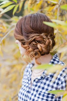 Side updo with braid across curly side bun.