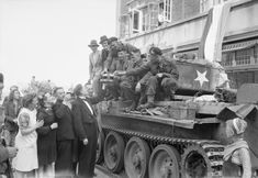 Dutch civilians offer drinks to the crew of a Cromwell tank of 2nd Welsh Guards during the liberation of Eindhoven, 19 September 1944.