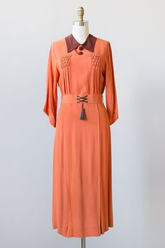 1930s dress features a vibrant combination of orange and brown. Large collar and buttons on the front add a nice touch. The bodice features smocking detail with vertical pleats. Matching belt with laced leather and tassel. Dress has godet pleats along the hem. Via Adored Vintage.