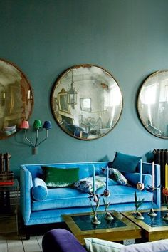 LOVE that blue sofa!  And those huge round antique mirror things that look like antique building security mirror things!