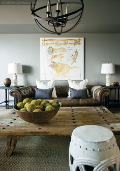 LEather and blue accent...Globe / spherical metal light. Vintage leather couch. Large antique print artwork on the wall! rustic wood table, white garden stool