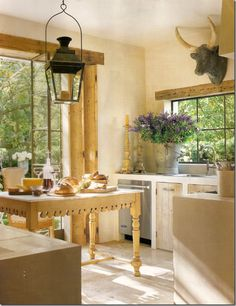 French country kitchen w/ antique butchers table, limestone floor, stucco walls, antique French lantern, and cow's head sculpture; Pam Pierce