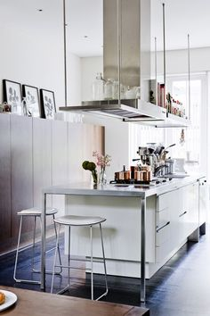 The beautiful floating shoulder height cabinets on the left. Genius. I don't believe the items stored on the rangehood structure wouldn't get coated with grime though. Particularly those glass bottles. Maybe she doesn't cook. Look at those gleaming cooper pots —case in point.