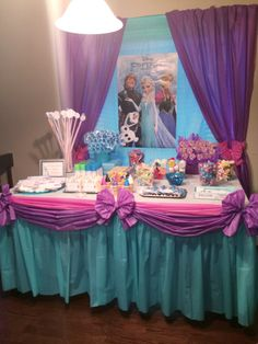Frozen birthday party ideas. Candy buffet / cake table with Anna and Elsa poster. Great use of plastic table cloths - curtains, table skirts and bows