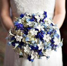 Blue and white, round, hand-tied bridal bouquet featuring light blue and dark blue delphinium, white stephanotis, and pearls.
