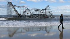 John Okeefe walks on the beach as a roller coaster that once sat on the Funtown Pier in Seaside Heights, N.J., rests in the ocean on Wednesday, Oct. 31, 2012 after the pier was washed away by Superstorm Sandy.