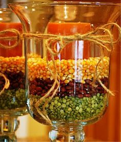 Fill hurricane vases with popcorn kernals, red beans, peas and a candle. Pretty and easy