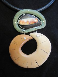 Robbin Smith and Warren Moellers' pendant from E-Bu Jewelry on The Polymer Arts blog. This pendant shows a wide variety of elements consisting of  a found bronze object, sterling silver, ebony, spiny oyster, polymer, and leather. www.thepolymerarts.com
