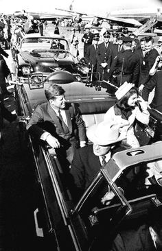 President John F. Kennedy and Jackie Kennedy ride in the limousine as they depart Love Field Airport. November 22, 1963