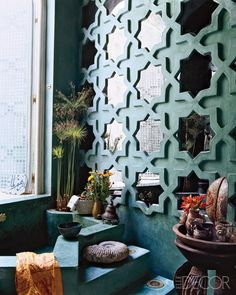 Islamic pattern enlarged to create wall design with mirrors in this teal bathroom.
