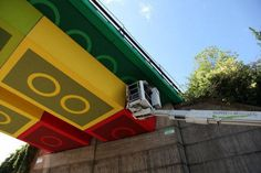 A crew in Germany paints a train bridge overpass to look like Lego bricks