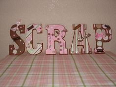 Wall Art - Scrapbook.com - What a clever idea! Wooden letters covered with scrapbook papers and finished off with ribbons and embellishments. Terrific wall art to make and color coordinate with your craft studio or space. #scrapbooking #crafting #diy