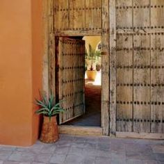A pair of vintage clavos-studded hacienda doors from Mexico opens to an arcaded courtyard at this  Austin, Texas, home.
