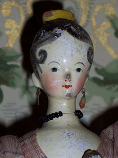 This FINE EXAMPLE has a DELICATELY CARVED WOODEN HEAD with painted and varnished features - a YELLOW TUCK COMB - BLACK PAINTED HAIR WITH LITTLE SPIT CURLS with her EARS EXPOSED! TINY LITTLE EARRINGS