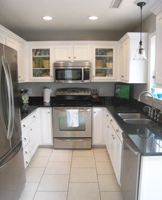 Stainless appliances, microwave hood, two glass cabinets. fabric wallpap, appliances, apartment kitchen, small kitchens, small kitchen makeover, wallpapers, wine bottles, white cabinets, blues
