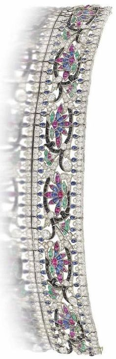 An Art Deco diamond and gem-set bracelet, by Van Cleef & Arpels.  The broad strap of pierced scrolling foliate design, with central buff top onyx and diamond undulating bough motif interspersed with flowering similarly-cut emerald, sapphire and ruby palmettes, to a circular-cut diamond and pear shaped cabochon sapphire border, 1924, French marks for platinum, 19.2cm long  Signature worn, with maker's mark MS flanking an ear of wheat in a lozenge and no.24647. Christie's.