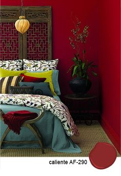 Benjamin Moore Caliente AF-290 on this bedroom's ruby red wall. Nice accent colors for the ruby red.  Add on turquoise bed color